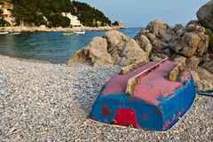 Upside Down Boat on the Rocky Beach Royalty Free Stock Photo