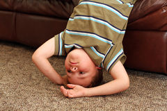 Upside down boy!. A 6-year-old boy is upside down, standing on his head, in the living room stock photography