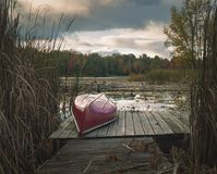 Upside down canoe at a dock. Upside down canoe and  dock at the lake waters edge on an autumn day Royalty Free Stock Photo