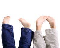 Upside down children feet. Legs and bare feet of two children upside down with white background Stock Photography