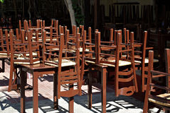 Upside Down. Closed restaurant with old fashioned brown wooden chairs set upside down on tables at sunny summer day Stock Photo