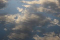 Upside down clouds. You`re not looking at the sky - look closer and you`ll see the ripples of the water, giving away the secrets. The clouds hint at rain - the Stock Photography