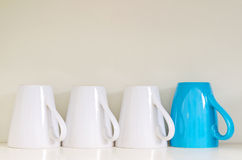 Upside down coffee and tea mugs with one standing out. Individuality represented by a single turquoise mug standing out from the rest Stock Photo