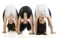 Upside-Down -- Content, Happy, Goofy. Three tween girls doing backbends together.  The first is content, the second smiles, the third is making a goofy face.  On Stock Images