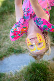 Upside down facepainting. Beautiful blond girl with yellow butterfly face-painting laughing stock photos