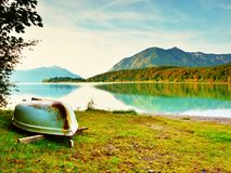 Upside down  fishing paddle boat on bank of Alps lake. Morning autumnal lake. Stock Photography
