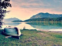 Upside down  fishing paddle boat on bank of Alps lake. Morning autumnal lake. Royalty Free Stock Photography