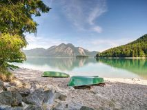 Upside down fishing paddle boat on bank of Alps lake. Smooth level stock image