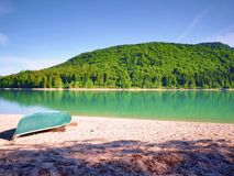 Upside down fishing paddle boat on bank of Alps lake. Smooth level stock photo