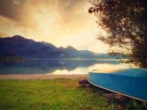 Upside down fishing paddle boat on bank of Alps lake. Smooth levelof autumnal lake. Royalty Free Stock Image