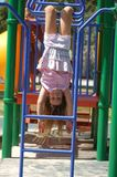 Upside-down girl on monkey bars Stock Images