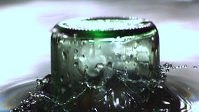 Upside down glass bottle falling in water stock video