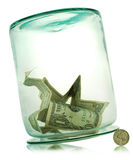 Upside Down Glass Money Jar. Money in a tipped over transparent glass jar Royalty Free Stock Image