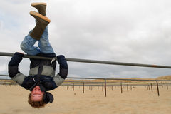 Upside down Kid. Boy (8) playing and hanging upside down on bicycle racks, doubling as climbing bars, in the dutch dunes. He is wearing winter clothing, photo is stock photos