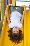 Upside down little girl on slide laughing Royalty Free Stock Photography