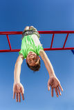 Upside down on the monkey bars. A happy young boy hangs upside down from the monkey bars Stock Photography