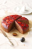Upside-Down Plum Cake. On a baking paper, with silver knife, on a light background Royalty Free Stock Photography