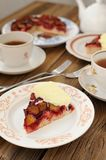 Upside down plum pie with ice-cream and black tea. With two long forks Royalty Free Stock Images