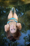Upside down portrait of bikini girl lying in shallow water. At bathing lake Royalty Free Stock Photo