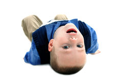 An Upside Down World. Small boy turns his world upside down to get a different and new view.  He is laying on an all white floor with his head tilted backwards Stock Photography