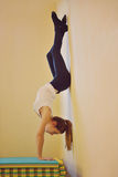 Upside down. Young woman standing upside down near the wall stock photo