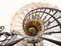 Upside view of indoor spiral winding staircase with black metal ornamental handrail Stock Images