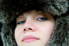 Upstage girl in a bih fur hat. Girl in a big fur hat that looks down on the camera Stock Image