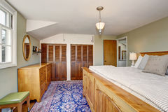 Upstairs bedroom with master wooden bed and built-in wardrobe. Royalty Free Stock Photos