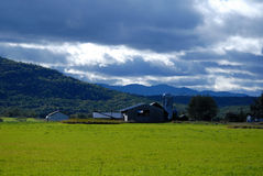 Upstate New York farm with tree covered Mountain with a blue clouded sky in autumn. Looking across a farmer`s field to the farm buildings with a large mountain royalty free stock images