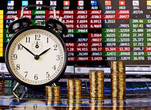 Uptrend stacks of golden coins, clock and financial chart. As background. Selective focus Royalty Free Stock Photography