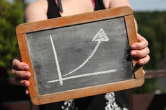 Upturn graph. Sketched with chalk on writing slate shown by young female Stock Image