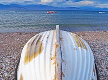 Upturned boat on Nikolaiika Beach and the Corinthian Gulf, Greece. A upturned boat sits on Nikolaika Beach near the blue waters of the Corinthian Gulf on the Stock Photos