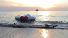 Upturned boat at the shore. Upturned boat is washed sand shore. Motorboat and sunset in background stock video