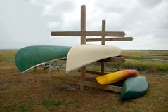 Upturned canoes on wooden rack Stock Photos