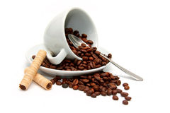Upturned cup with coffee beans Stock Photography