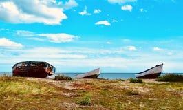Upturned fishing boats on heath near shore royalty free stock photography