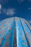 Upturned Hull of a Rowing Boat. Upturned hull of a blue weathered rowing boat, it's bow pointing up to a dark blue sky with white clouds royalty free stock photography