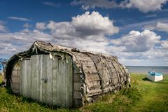 An upturned rowing boat renovated into a house. stock photo