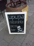 Restaraunt sign in Venice. Upupa restaurant pizza bar sign leaning against barrel in Venice street stock images