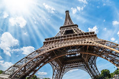 Eiffel Tower. Upward distorted exterior view of the Eiffel Tower from its base to the top, with multiple rays of sunshine coming from the sun in the far left Royalty Free Stock Images