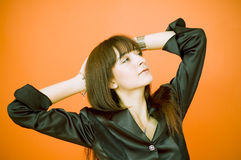 Upward Gaze. Young woman with her hands on the back of her head and elbows extended, looking upward to her left. Taken in studio, isolated on orange background stock photography