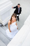 Upward looking of smiling bride. Groom behind Stock Images