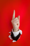 Upward pointing finger. Close of hand with upward pointing finger protruding through hole in red background Stock Photos