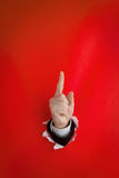 Upward pointing finger. Close of hand with upward pointing finger protruding through hole in red background Royalty Free Stock Image