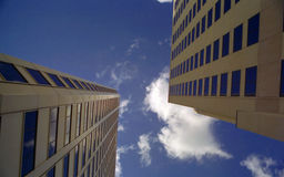 Upward Between Skyscrapers. Looking up at clouds and blue sky between two skyscrapers in New Orleans Stock Images