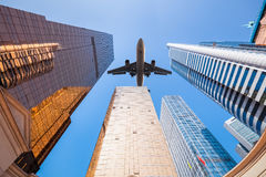 Upward view of airplane and modern building Royalty Free Stock Photo