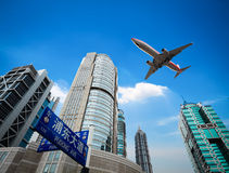 Upward view airplane with modern building Royalty Free Stock Image