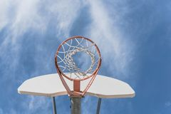 Close-up basketball hoop rim and backboard under cloud blue sky. Upward view a basketball hoop in public arena at community park in Irving, Texas, USA. Lookup of Royalty Free Stock Image