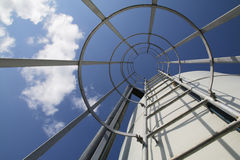 Upward view from a caged ladder of structure Stock Photography