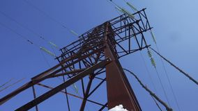 Upward view diagonally to the power line and pylon against a blue sky with clouds